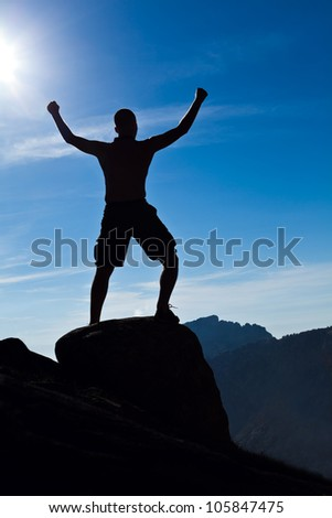 Man climbing in mountains, arms outstretched, success concept. Silhouette of climber and blue summer sky, extreme sport and exercising outdoors. - stock photo