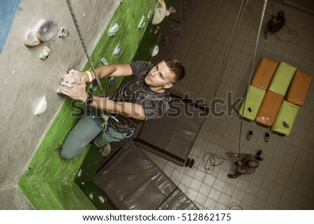 man climbing on a climbing gym. view from above.