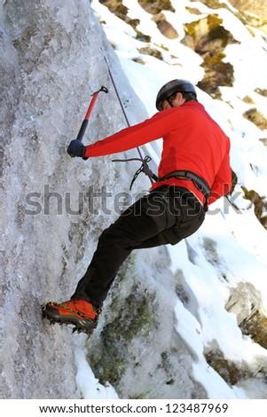man climbing on frozen waterfall in winter - stock photo