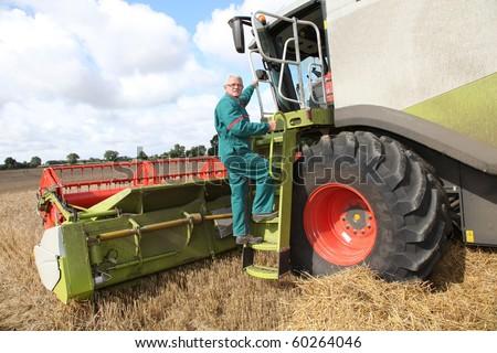 Man climbing on harvesting machine with computer - stock photo