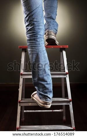 Man climbing on ladder - stock photo
