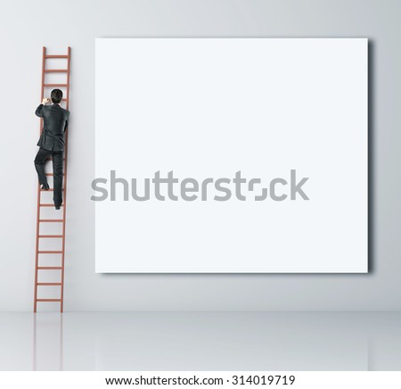 man climbing on ladder and blank poster - stock photo