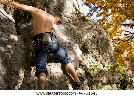 Man climbing or bouldering  a rock in the alps on a beautiful autumn day in the mountains - stock photo