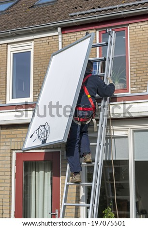 man climbing the ladder to the roof with solar panel - stock photo