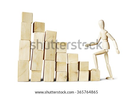 Man climbing up to high stack of blocks. Abstract image with a wooden puppet - stock photo