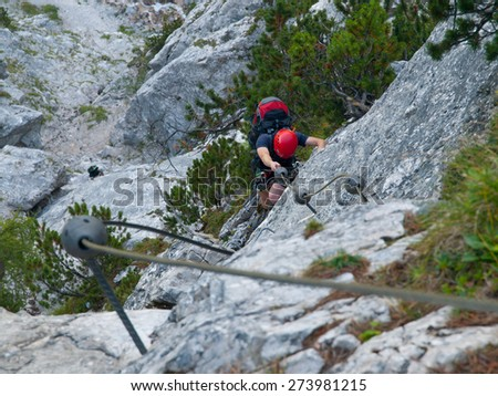 Man climbing vertical wall on via ferrata, view from above - stock photo