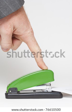 Man clipping some office papers with green staple - stock photo