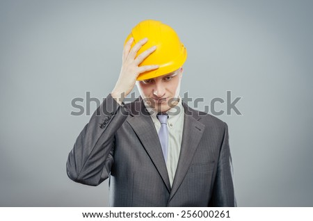 man close-up in yellow helmet headache, holding his head by hand - stock photo