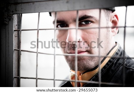 Man Close - Up Portrait. Behind An Iron Lattice - stock photo
