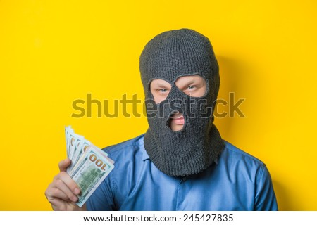 man close up thief in a mask and a blue shirt on a yellow background looks slyly to the camera. Mimicry. Gesture. photo Shoot - stock photo