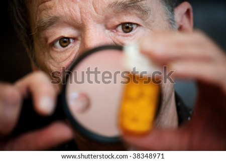 Man closely examining instructions on prescription medications - stock photo