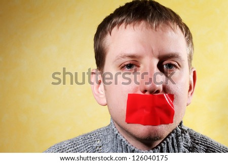 man closes his mouth red tape, creative, symbolizing the fight for freedom of speech and against censorship - stock photo