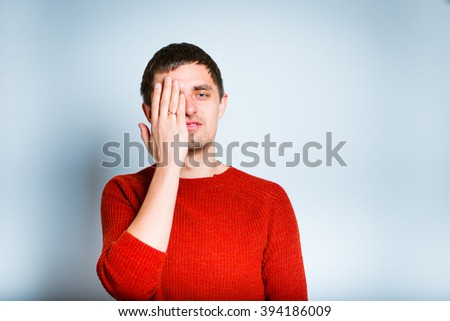 man closes tired eyes hands, isolated on a gray background - stock photo