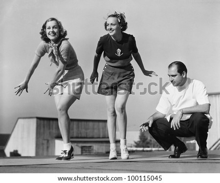 Man coaching two female dancers