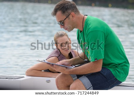 man coaching young water skier