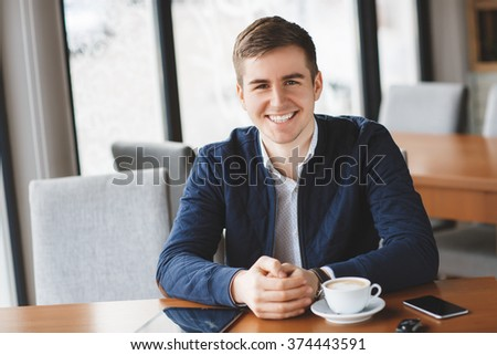 man, coffee, smile. Man in cafe looking into the camera. Interior portrait of a hot looking relaxed happy male model with a cup of morning coffee.  - stock photo