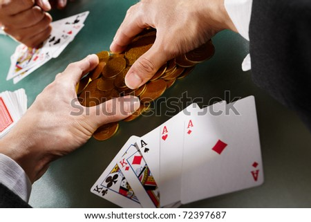 Man collecting his winning money after playing poker - stock photo