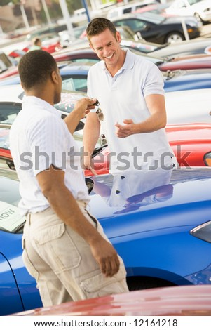 Man collecting new car from dealer - stock photo