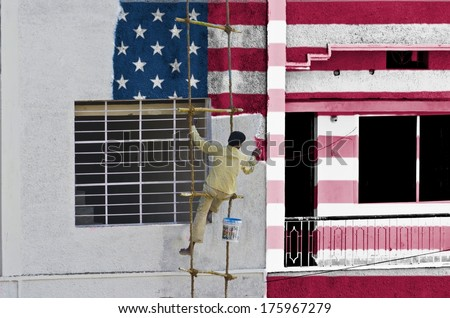 Man coloring or painting flag of United states manually on wall hanging on a rope ladder - stock photo