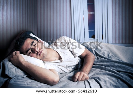 Man comfortably sleeping in his bed at night - stock photo