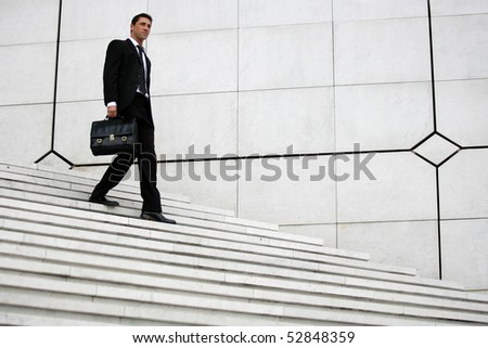 Man coming down stairs with a suitcase - stock photo