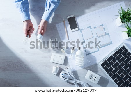Man comparing an obsolete incandescent bulb and a CFL energy saving lamp, house project and solar panel - stock photo