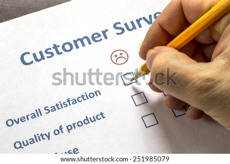 Man completing a customer survey with check boxes selecting to show his dissatisfaction - stock photo