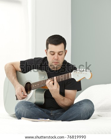 Man composing music using electric-acoustic guitar - stock photo
