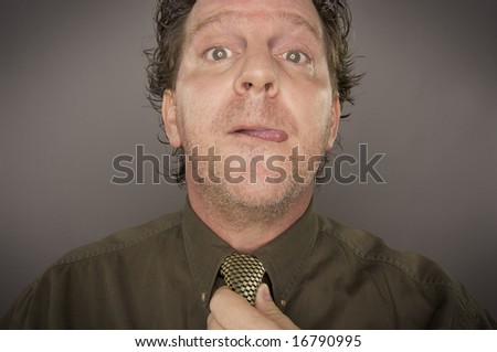 Man Concentrating Fixing Tie on a Grey Background