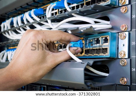 man connecting network cable to switch - stock photo