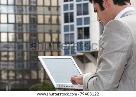 Man connecting to Internet outdoors - stock photo