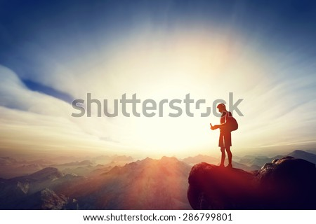 Man connecting with his smartphone on top of the mountain. Internet, communication, texting from remote place concepts. - stock photo