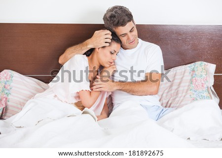 Man consoles his wife lying bed in bedroom, couple consoling, husband embrace comforts his woman - stock photo