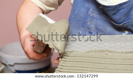 Man Construction worker is tiling at home, tile floor adhesive