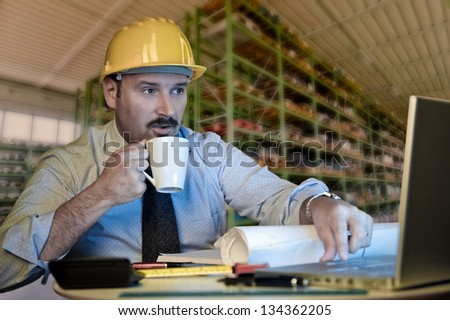 Man consults a laptop. In Background factory indoor.drink a cup - stock photo
