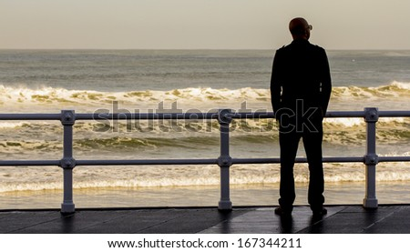 Man contemplating the sea at sunrise