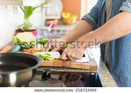 Man cooking and cutting veggies for lunch - stock photo