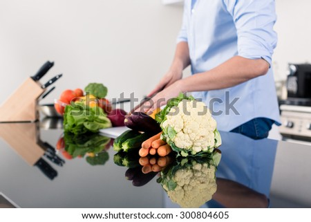 Man cooking and preparing salad in kitchen - stock photo