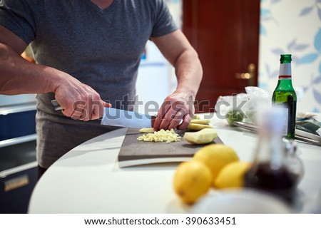 Man cooking at home, chopping ginger for a recipe - stock photo