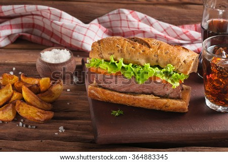 Man cooking big sandwich on a wooden table