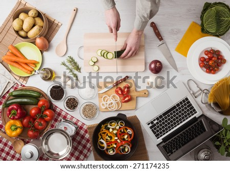 Man cooking in the kitchen and slicing vegetables on a chopping board, top view - stock photo
