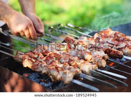 Man cooking marinated shashlik, lamb meat grilling on metal skewer, close up - stock photo