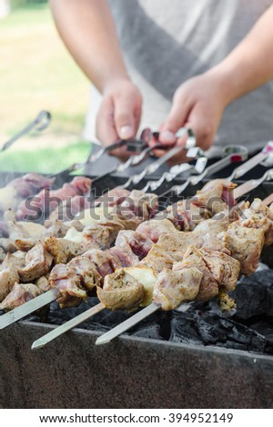 Man cooking marinated shashlik or shish kebab, chiken meat grilling on metal skewer, close up. Selective focus - stock photo