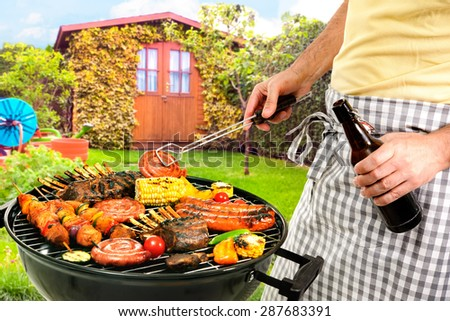 Man cooking meat on barbecue in front of backyard - stock photo