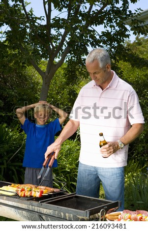 Man cooking on barbeque by son with hands on head, smiling - stock photo