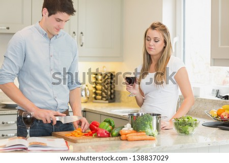 Man cooking with woman drinking red wine in kitchen - stock photo
