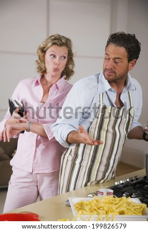 Man cooking, woman pointing watch