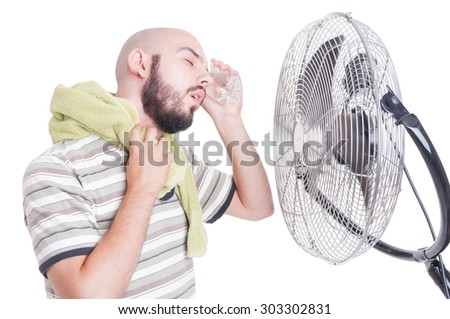 Man cooling his head with cold water bottle and fan or blowing cooler - stock photo