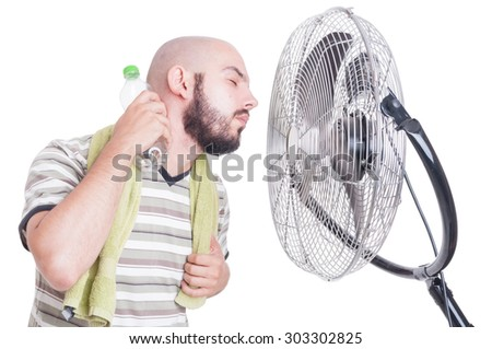 Man cooling his neck with cold water bottle and fan or blowing cooler - stock photo