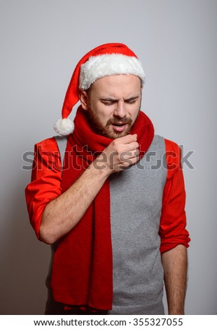 Man coughs. is ill. Happy Businessman wearing a Santa hat on New Year's corporate parties. Studio photo, isolated on a gray background - stock photo